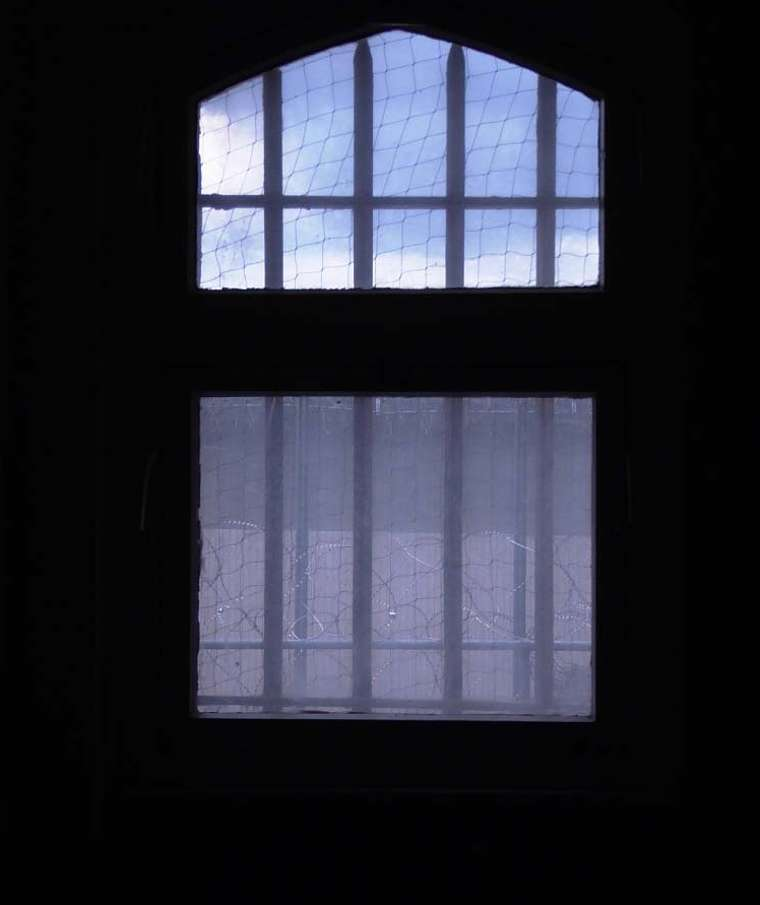 Photo from a prison cell looking out the barred window.